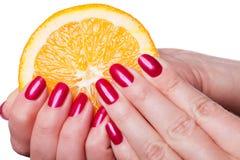 La main avec des ongles manucurés touchent une orange sur le blanc images stock