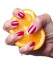 La main avec des ongles manucurés touchent une orange sur le blanc photo stock