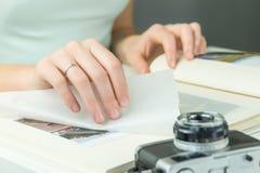 La main avec la bague de fiançailles tourne la page de l'album photos de famille Image libre de droits