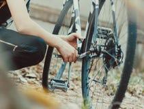 La main avec la clé répare la bicyclette cassée Photographie stock libre de droits