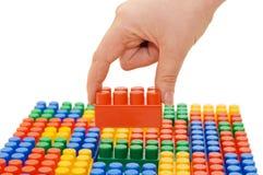 La main avec le bloc de jouet a isolé Photo stock