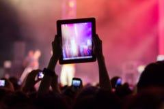 La main avec un comprimé enregistre la musique en direct photo libre de droits