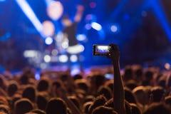 La main avec un smartphone enregistre le festival de musique en direct image stock