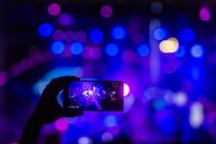 La main avec un smartphone enregistre le festival de musique en direct images stock