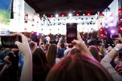 La main avec un smartphone enregistre le festival de musique en direct, concert vivant, jeunesse heureuse images stock
