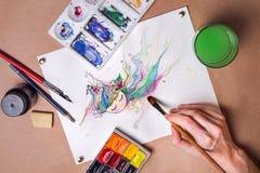 La main avec une brosse dessine l'illustration avec des aquarelles Images libres de droits