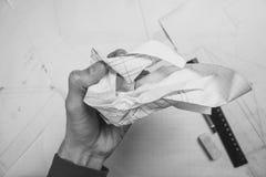 La main chiffonne le papier au-dessus de la table photo libre de droits