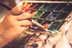La main créative de peintre d'enfant avec le pinceau peint le développement d'art d'enfant de concept à l'école d'art image libre de droits