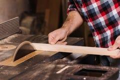 La main cultivée d'un charpentier travaillant à un bourdonnement électrique a vu couper quelques conseils Photos stock