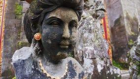La main a découpé la sculpture en pierre solide de la femelle dans le vieux temple sur Bali en Indonésie banque de vidéos