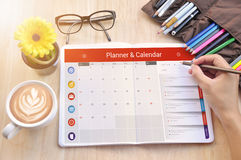 La main d'affaires écrivent sur le carnet avec le planificateur de calendrier Photo libre de droits