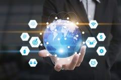 La main d'affaires avec des icônes d'application réseau connectent et de globes photographie stock libre de droits
