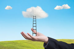 La main d'affaires avec l'échelle conquièrent le succès sur le nuage Photographie stock libre de droits