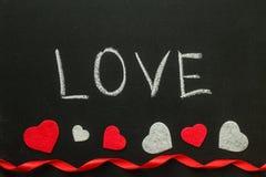 La main d'amour écrit sur le panneau de craie Images stock
