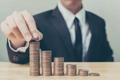 La main d'homme d'affaires mettant la pile de pièce de monnaie intensifient l'augmentation épargnent l'argent, Photo stock
