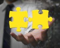 La main d'homme d'affaires montrant à l'or deux 3D le puzzle denteux rapièce Photo stock
