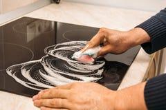 La main d'homme lave le fourneau électrique noir moderne avec du savon Photos libres de droits