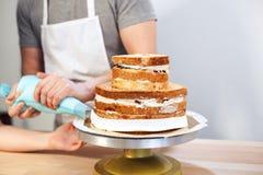 La main d'homme mise a fouetté la crème sur la croûte de gâteau, tir étroit d'une main d'humain givrant un gâteau avec la crème f Photo libre de droits