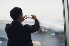 La main d'homme prennent la photo de l'avion utilisant le téléphone portable Photo de concept de tourisme Images libres de droits