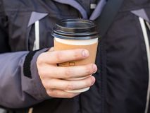 La main d'homme tenant la tasse de papier de emportent, printemps, fond brouill? image libre de droits