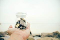 La main d'image tenant le pot en verre contiennent avec la pièce de monnaie à la plage Photos libres de droits