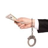 La main d'isolement d'un homme d'affaires dans des menottes prend l'argent de paiements illicites Images stock
