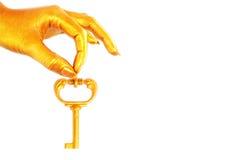 La main d'or retient une clé sur la réussite d'affaires Images stock