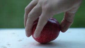 La main d'un agriculteur prend une poire verte mûre sur une table rurale blanche dans la perspective d'un jardin vert sur l'extér banque de vidéos
