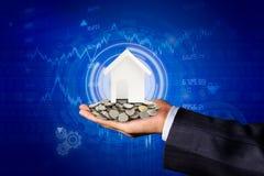 La main d'un homme d'affaires avec des pièces de monnaie sur ses mains et d'une maison modèle placée sur une pièce de monnaie photographie stock
