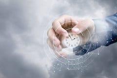 La main d'un homme d'affaires dans le ciel montre l'horloge Photo libre de droits