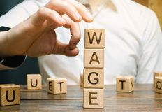 La main d'un homme d'affaires enlève les blocs en bois avec le salaire de mot Concept de réduction de salaire Réductions de salai photographie stock libre de droits