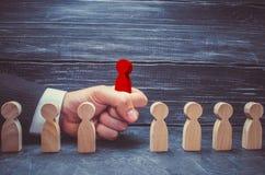 la main d'un homme d'affaires prend un chiffre en bois rouge d'un homme Le concept des travailleurs de recherche, de location et  photographie stock