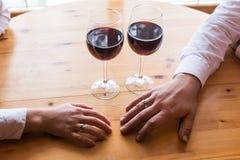 La main d'un homme avec un anneau s'étend à la main du ` s de femme Deux glaces avec le vin rouge Dîner romantique, une date Image stock
