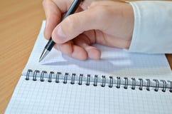 La main d'un homme dans une chemise blanche écrit le texte avec un stylo noir dans un carnet avec une spirale sur un plan rapproc image stock