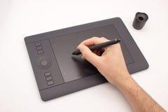 La main d'un homme dessine un stylet sur une tablette graphique photo stock