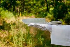 La main d'un serveur dans un gant blanc tient un couteau en métal sur la nature Photos libres de droits