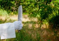 La main d'un serveur dans un gant blanc tient un couteau en métal sur la nature Images libres de droits