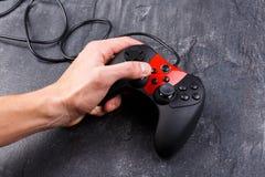 La main d'un type tenant une manette de la console de jeu et poussant les boutons Plan rapproché Photographie stock libre de droits