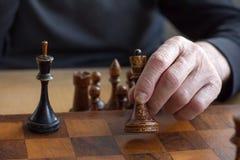 La main d'un vieil homme met le chiffre d'un roi noir sur la perte de reconnaissance de conseil, simulations de gestion de concep photo libre de droits