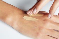 La main d'une femme appliquant la crème sur la peau image stock