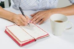 La main d'une femme avec un stylo écrit en son journal intime Après sur photographie stock