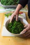 La main d'une femme jetant le chou frisé en l'air massé frais verdit dans une cuvette en céramique blanche Images stock