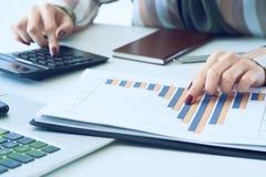 La main d'une femme se dirigeant sur le diagramme de compte rendu succinct et calculer des finances en plan rapproché de bureau images libres de droits