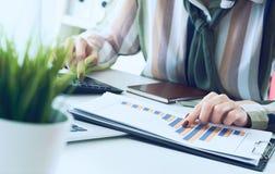 La main d'une femme se dirigeant sur le diagramme de compte rendu succinct et calculer des finances en plan rapproché de bureau image libre de droits