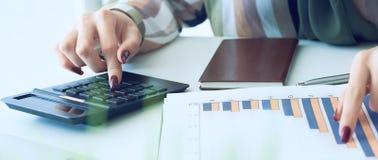 La main d'une femme se dirigeant sur le diagramme de compte rendu succinct et calculer des finances en plan rapproch? de bureau photo stock