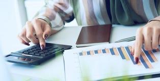 La main d'une femme se dirigeant sur le diagramme de compte rendu succinct et calculer des finances en plan rapproch? de bureau photos libres de droits