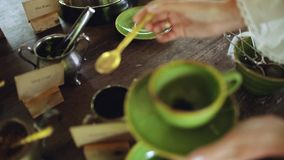 La main d'une femme tient une tasse verte de porcelaine Avec l'autre main il met une cuill?re ? caf? des feuilles de th? banque de vidéos