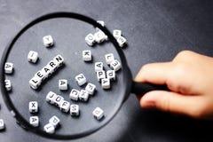 La main d'une petite fille avec ci-dessus en verre de loupe apprennent le mot des cubes en lettres de plastique, désir d'apprendr photos stock
