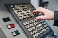 La main d'utilisation d'opérateur tourne le contrôle de commutateur de cadran au panneau pour ajustent le paramètre de la machine Image libre de droits