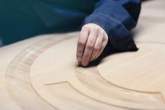 La main dans des combinaisons bleues polit la porte en bois images libres de droits